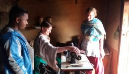 In the huts, the sewing machines donated during the last visit are examined. Ludmila tries one of the machines.