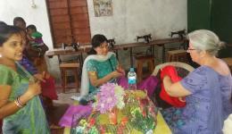 Ingrid und Erni sehen sich die fertigen Kleidungsstücke der jungen Frauen an, welchen der FriendCircle WorldHelp vor Jahren Nähmaschinen zur Verfügung gestellt hat.
