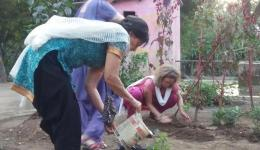 Erni, Katrin and Ingrid planting three fruit trees next to the well, which was drilled by FriendCircle WorldHelp a few years ago and now allows gardening. This is to bring happiness and blessings to the whole village.