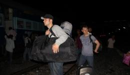 After a while, the train to Raxaul finally arrives. The friends cross the tracks with their luggage and board the train.