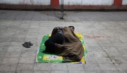 """Two Indians make themselves comfortable on the platform under a blanket and a plastic tarp,  waiting for their train. Note the imprint """"Wellness"""" on the plastic tarp;-)"""