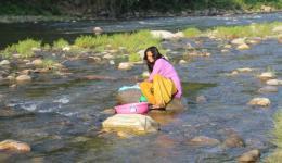 Sanju doing the laundry at the riverside.