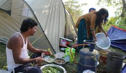 """The """"field kitchen"""" in operation. Ramavarai cutting green leaves brought by friendly villagers for breakfast. Now we will get food after the night in the tent and a shower in the river."""