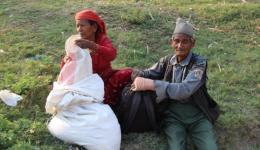 The 90- year-old man and his wife sitting sadly in the grass. We learn that he is not able to carry his bags himself.