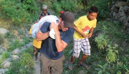 Florian carrying the bag with the food ration to a remote hut of a 90-year-old couple.