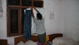 Mingmar carefully fixing a plastic sheet on the window without glass so that it does not rain into the room and on the beds.