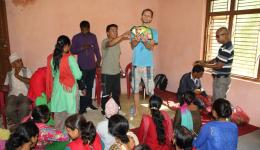 Michael and Mingmar distributing the packets. Madan Ji helps to bundle the seed packets. Sunny and Alexandra are taking pictures.