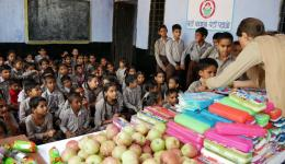 Many children from particularly poor families are happy to receive school materials and apples.