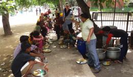 Soup kitchen in Delhi. At the street stand Katrin gets one meal after the other and hands over a full plate to everyone present.
