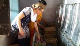 In Chota-Phool. Katrin und die Nachhilfe-Lehrerin sehen die Schulmaterialien für die Kinder durch. In großen Kisten werden auch Zahnbürsten etc. gelagert und nur bei Bedarf an die Kinder ausgegeben.