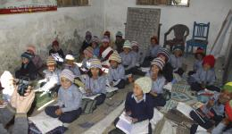 View of the classroom. The children are sitting on the floor, writing utensils on their legs.