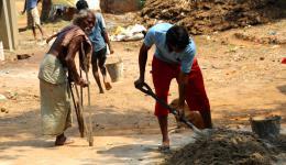 Die nicht leprabetroffenen Männer der Kolonie helfen beim Anrühren des Betons für den Verputz.
