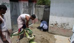 Innerhalb der Ummauerung der Sanitäranlage wird nun noch der Untergrund vor den Toiletten mit einer feinen Betonschicht geebnet, sodass das Wasser der Pumpe durch ein Loch an der Seite abfließen kann.