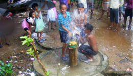 Jaganath Kolonie: Obwohl es ohnehin regnet springen beim Testlauf der sofort einwandfrei funktionierenden Pumpe einige Kinder vor Freude spontan unter den Wasserstrahl...