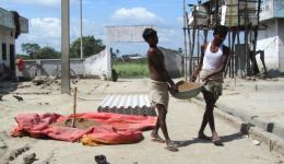 Mit indischen Tasslas (Metallschüsseln) tragen die Männer des Lepradorfes den Sand zur Baustelle.