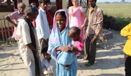 Auch die Mutter mit dem unterernährten Kind freut sich sehr über die Brote und Äpfel für ihre Kinder.
