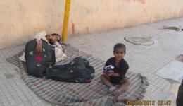 Ein kleiner Junge, der mit seine Mama auf der Straße lebt, freut sich über das Essen.