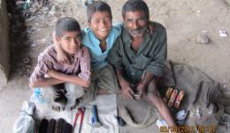Schuhputzer mit seinen beiden Söhnen, die drei freuen sich über Kekse