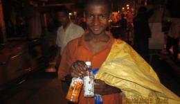 Junger Müllsammler freut sich über zwei leere Flaschen und eine Packung Kekse