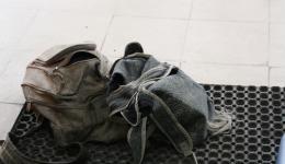 Die alten Rucksäcke, die viele Löcher haben, von zwei Kindern die Schuhe putzen