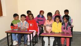 Die Kinder stürzen sofort in das neue Zimmer. Sie mögen die gelb- pink angestrichenen Bänke sichtlich.