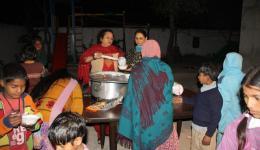 Mitarbeiterinnen vom Kinderheim teilen hier den Milchreis aus. Die Kinder stellen sich in der Reihe an...