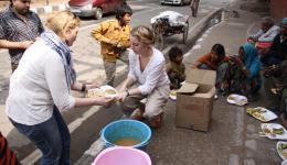 Claudia und Kati teilen zusammen mit Chetan und einem Freund und unserem Fahrer das Essen aus. Völlig verdreckte Kinder, teilweise ohne Hosen sitzen am Straßenrand mit ihren Tellern vor sich und essen.