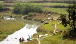 Fotos von der Zugfahrt. Menschen baden sich im Fluss.