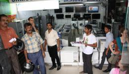 In einem Laden für Waschmaschinen. Die Indsutriewaschmaschinen gibt es nur im Prospekt. Dr. Abraham wird den besten Preis verhandeln und wir werden zurückkehren um ein Foto der vom Freundeskreis Indienhilfe gespendeten Maschine zu machen.