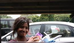 Wie viele andere Kinder verdient dieses Mädchen ihren Lebensunterhalt mit kleinen Verkäufen zwischen den Autos. Es freut sich sehr über die Kekse...