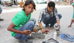Schuhputzerjungen reparieren und säubern Michaels ausgerissene Sandalen mit hoher Geschicklichkeit und Fleiß.