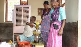Schwer an Händen und Füßen gezeichneter Mann gießt mit aller Hingabe das vom Freundeskreis Indienhilfe gespendete Speiseöl in die mitgebrachten Gefäße der Familien.