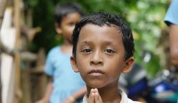 Ein kleiner Junge faltet die Hände zum indischen Gruß.
