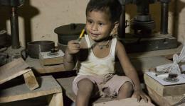Der kleine Sohn von Anil schaut seinem Papa interessiert bei der Arbeit zu.