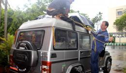 Der Taxifahrer und Guido verzurren das Gepäck und die Regenplane für die mehrstündige Fahrt nach Bhubaneswar.