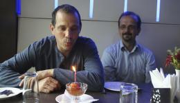 """Christian lächelt, als Guido seine Geburtstagskerze auf dem """"Gulab Jamun"""" (indische Süßigkeit) ausbläst. Christians nächster Geburtstag ist noch mehrere Wochen entfernt."""