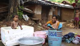 Eine Mutter wäscht ihre Wäsche, während ihr Kind in einem Bottich aus Styropor badet.