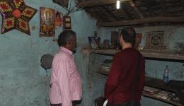 Kurz vor unserer Abfahrt zum Hotel zeigt Umesh Nayak, einer unserer Mitarbeiter, Guido sein Haus. Umesh und Guido betrachten ein Foto von Umeshs verstorbener Mutter im Hintergrund.