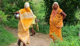 Eine Frau des Dorfes trägt Wasser von einem Brunnen zu ihrer Hütte. Ein wenig Wasser steht für Kochen und Waschen zur Verfügung. Zu wenig für die Bewirtschaftung der Felder während der Trockenperiode des Jahres.