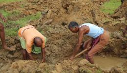 Die Erde wird mit Harken aufgelockert und aus dem Graben geworfen. Durch vereinzelte Regenschauer, den Vorboten des Monsun-Regens, entstehen bereits knietiefe Pfützen in den Gräben.