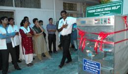 Dr. Abraham neben der Waschmaschine mit weiteren Mitarbeitern des TLM Hospitals (TLM=The Leprosy Mission)