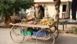 Ein Mann fährt mit seinem rollbaren Tisch, um Gemüse zu verkaufen. Ein idyllischer Anblick.