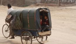 Morgens, wenn die Schule beginnt, fahren kleine, kreativ gebaute, nicht- motorisierte Fahrzeuge zielgerichtet in eine bestimmte Richtung. So viele Kinder wie möglich fasst das kleine Gefährt und immer wieder fragt sich Alexandra wie der Fahrer das schafft