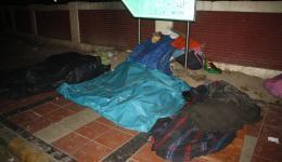 Unter Plastikplanen schlafende Menschen