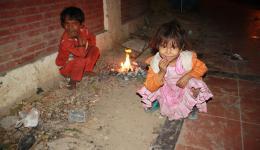 Am Feuer in der Nacht wärmen sich die kleinen Kinder.