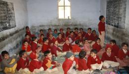 Ein Junge rezitiert unentwegt laut die Buchstaben des Alphabets und die anderen Schulkinder antworten.