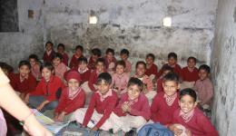 """Die Kinder sitzen in Reihen am Boden, ihre Schultaschen vor sich als """"Tisch""""."""