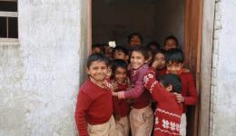 Aus mehreren Klassen strömen kleinere und größere Kinder herbei und scharen sich neugierig um die Besucher.