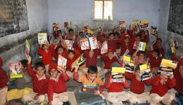 Glücklich halten die Kinder ihre neuen Schulsachen in die Kamera.