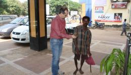 10.11. - Christian gibt dem Obdachlosen vor unserem Hotel in Bhubaneshwar ein paar Rupies.